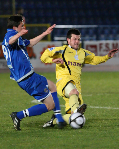 Neil Cousins slides in to tackle George Beavon